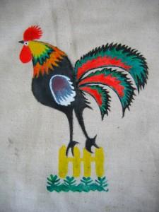 Kogucik malowany farbami do tkanin, na płóciennej siatce.